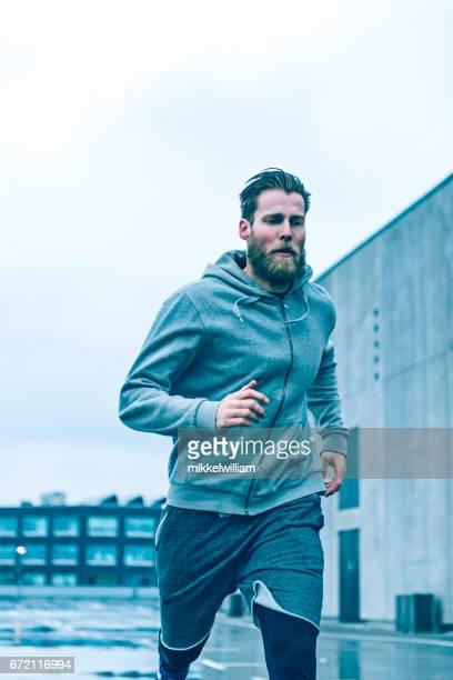 Loper sprints snel als hij buiten op een grijze dag loopt