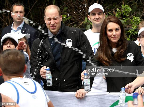 A runner squirts water towards Britain's Prince William Duke of Cambridge and Britain's Catherine Duchess of Cambridge as they hand out water to...