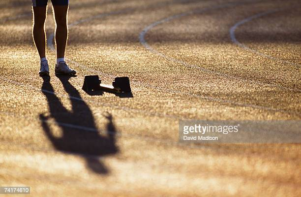 """Runner standing behind starting block, low section"""