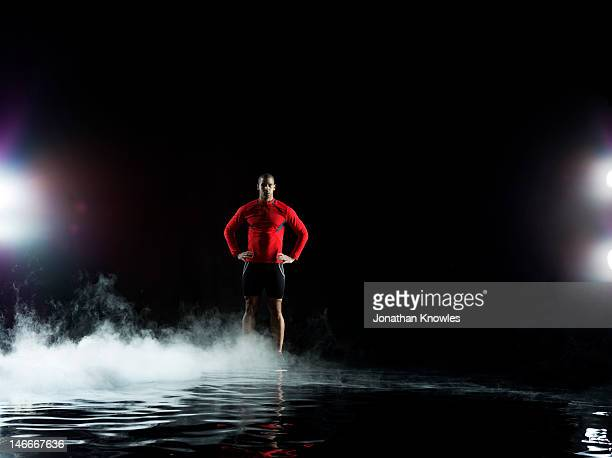 Runner standing in water, misty night
