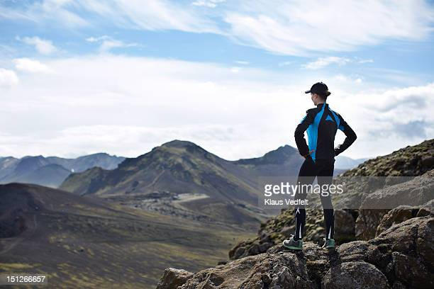 Runner standing on top of mountain looking out