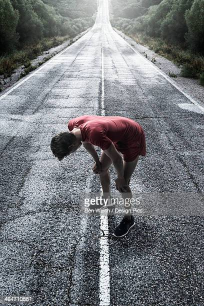 A Runner Stops To Take A Break On A Wet Road