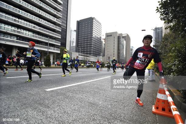 A runner streches on the Hibiya street as he competes during the 12th Tokyo Marathon in Tokyo Japan on February 25 2018