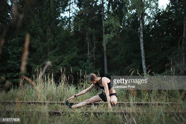 Runner stretching in forest before training run