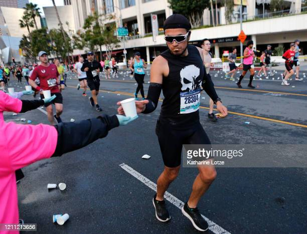A runner takes a cup of water on Grand Avenue during the 2020 Los Angeles Marathon on March 08 2020 in Los Angeles California