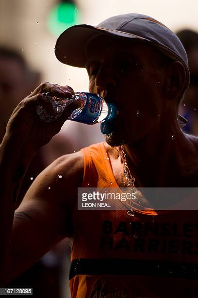 A runner takes a drink during the 2013 London Marathon in central London on April 21 2013 Tens of thousands of runners flowed through the British...