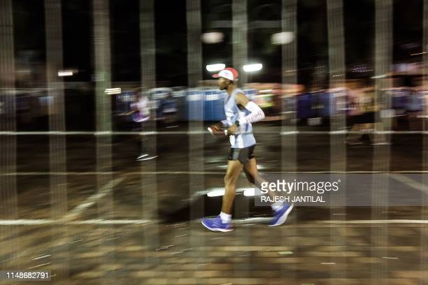 Runner takes part in the 94th edition of the Comrades Marathon between Durban and Pietermaritzburg in Durban on June 09, 2019. - The annual...