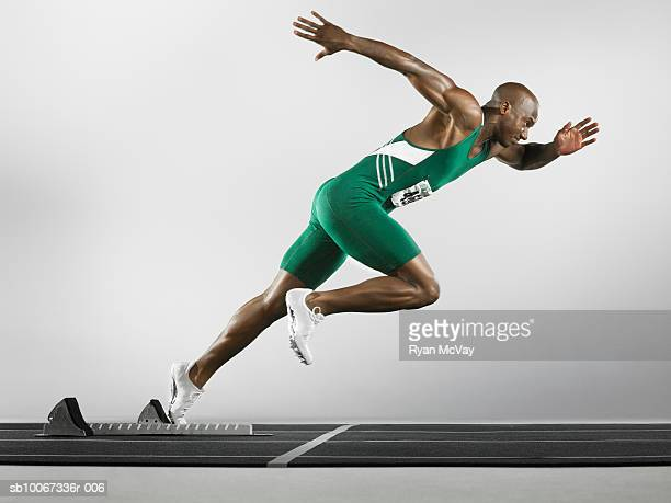 Runner taking off on track (studio shot)