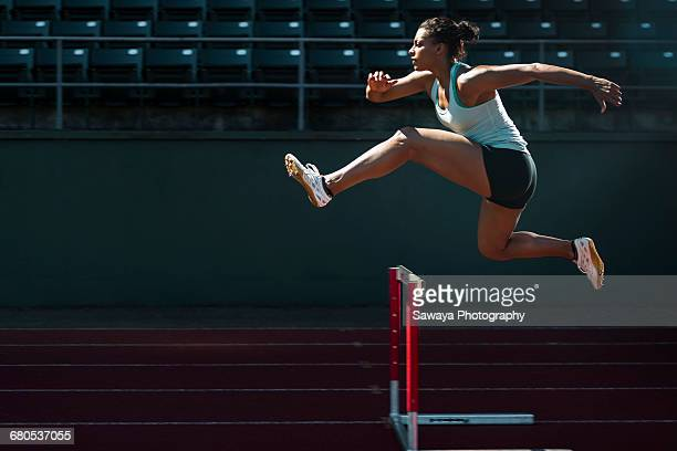 a runner taking on the hurdles. - training course stockfoto's en -beelden