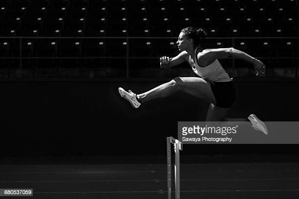 a runner taking on the hurdles. - atleta imagens e fotografias de stock