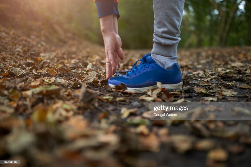 Runner touching toes with hands, close up. : Stock Photo