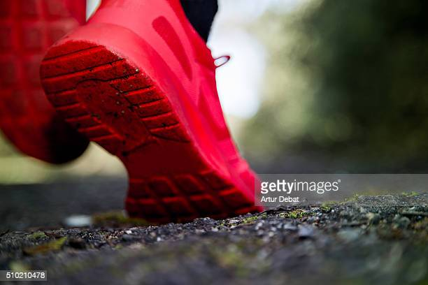 Runner training in the outdoor with red trainers in the black asphalt with view from the ground.