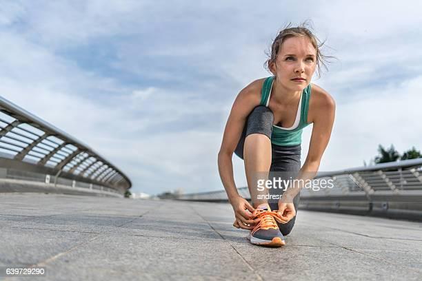 Runner tying her shoelace