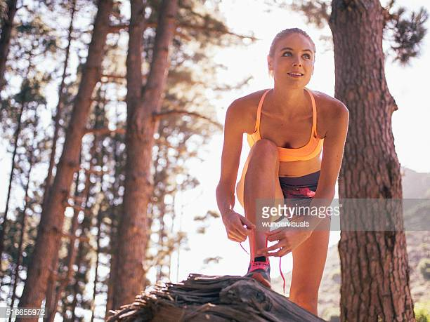 Läufer Binden Ihre Schnürsenkel und schaut an das Gelände vor