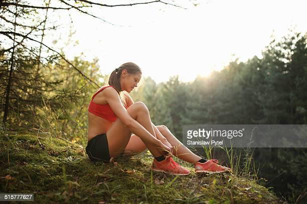 Runner tying her shoes, preparing for training run