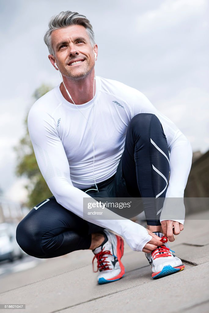Runner tying his shoelace : Stock Photo