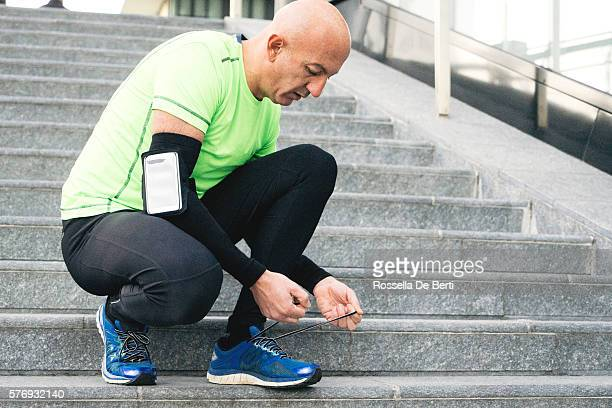 Runner Tying His Shoelaces, Cityscape On Background
