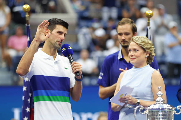 Runner up Novak Djokovic of Serbia speaks as Chris McKendry looks on during the trophy ceremony after being defeated by Daniil Medvedev of Russia...