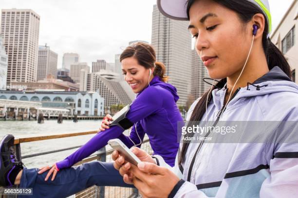 Runner using cell phone at waterfront, San Francisco, California, United States