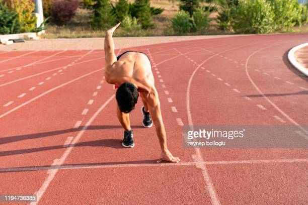 runner using starting block to start his run on race track. runner using starting block to start his run on running track in a stadium. athlete starting his sprint on an all-weather running track. - all weather running track stock pictures, royalty-free photos & images