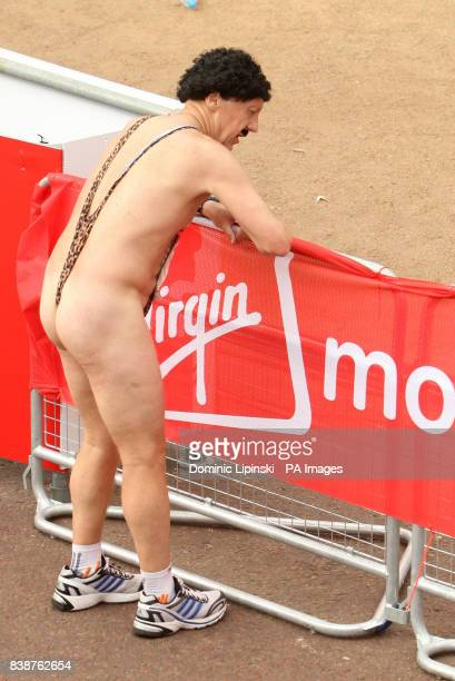 CONTENT* A runner wearing a 'mankini' recovers after finishing the 31st Virgin London Marathon in London