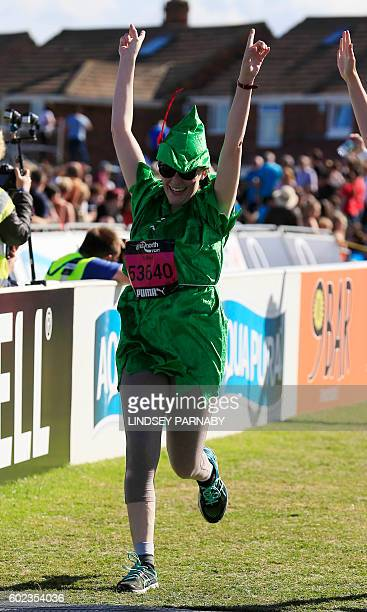 A runner wearing fancy dress crosses the finish line in the Great North Run halfmarathon in South Shields north east England on September 11 2016 The...