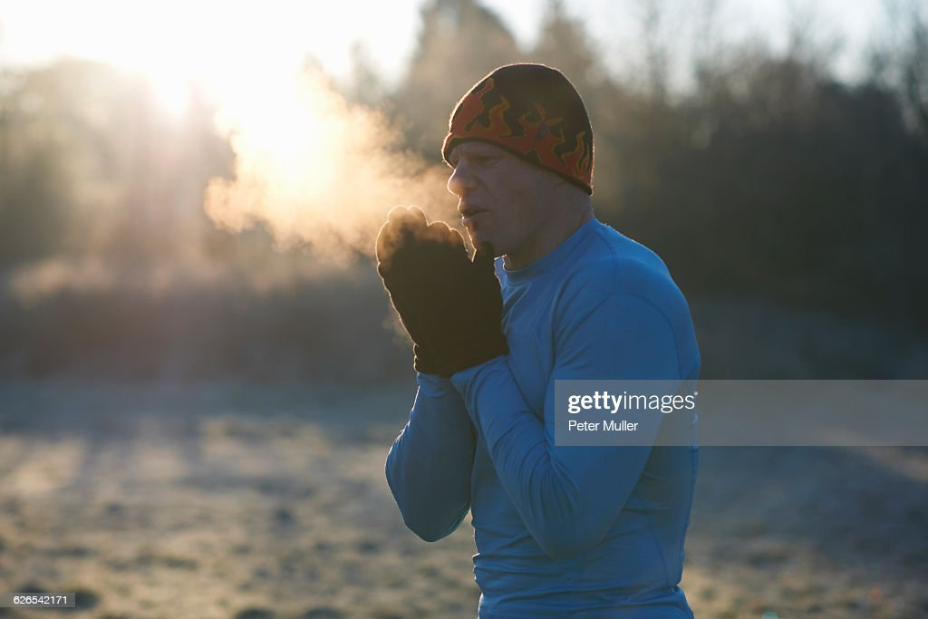 Runner wearing knit hat and gloves, rubbing hands together, breathing cold air : Stock Photo