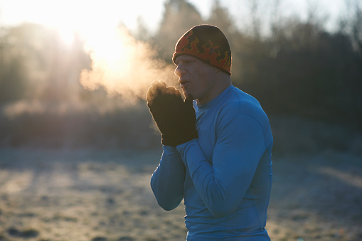 Runner wearing knit hat and gloves, rubbing hands together, breathing cold air - gettyimageskorea