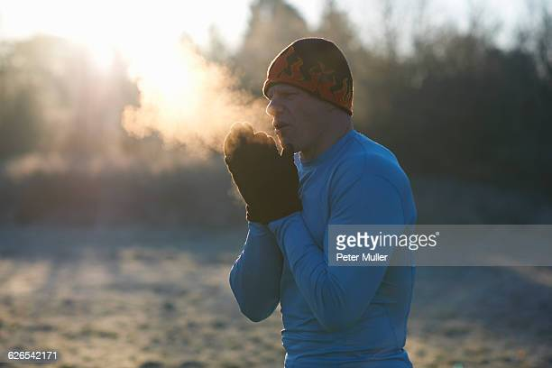 runner wearing knit hat and gloves, rubbing hands together, breathing cold air - kälte stock-fotos und bilder