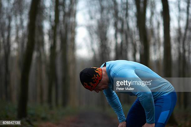 runner wearing knit hat and spandex bending forward hands on knees exhausted - hand on knee stock pictures, royalty-free photos & images