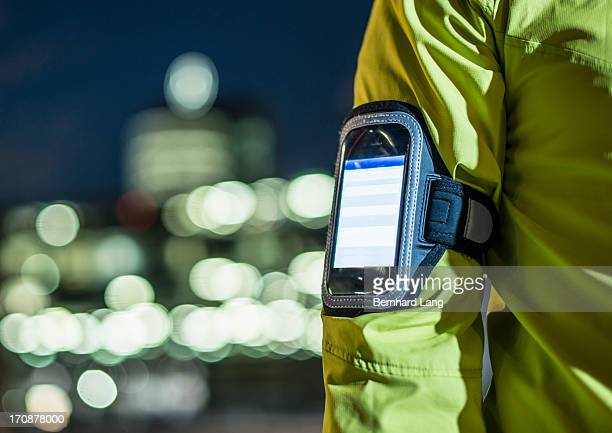 Runner wearing smartphone on arm in city