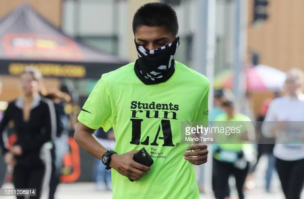 A runner wears a face mask while jogging in the Los Angeles Marathon which was allowed to continue by health officials in spite of coronavirus...