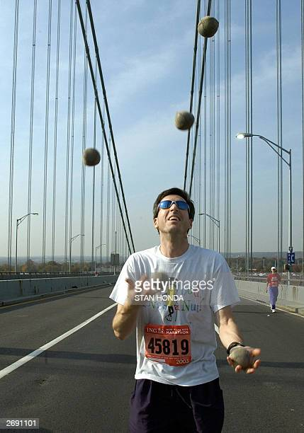 A runner who gave his name as Barry juggles balls as he makes his way over the VerrazanoNarrows bridge from Staten Island to Brooklyn after the start...