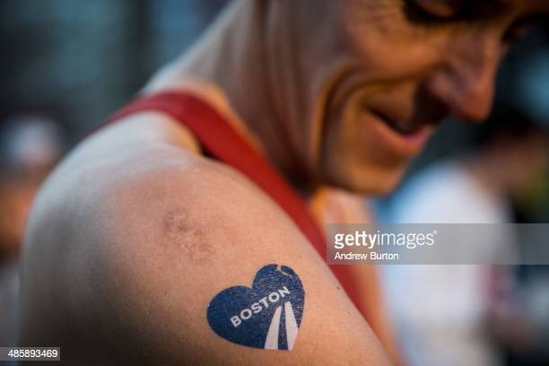A runner with a temporary Boston Marathon tattoo gets ready to run the 118th Boston Marathon in the Boston Commons on April 21 2014 in Boston...