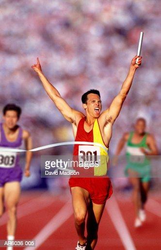 runner with baton crossing finish line stock photo