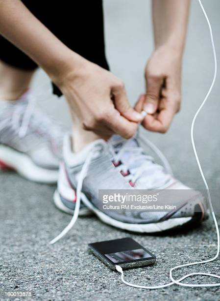 Runner with headphones tying her shoes