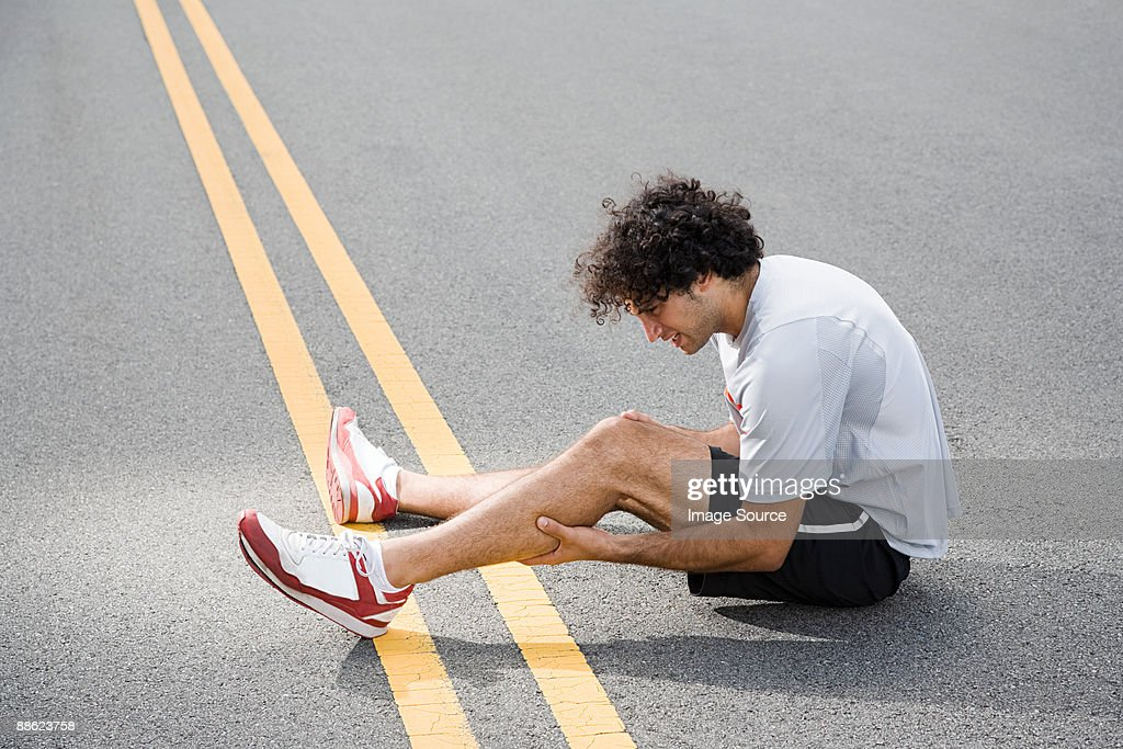 Runner with injured leg : Stock Photo