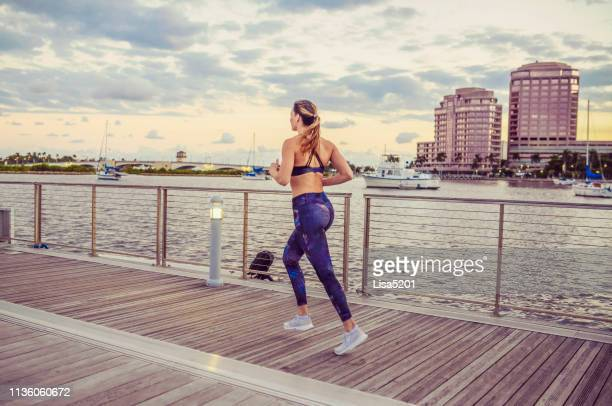 runner, woman, on the waterfront exercising - west palm beach stock pictures, royalty-free photos & images