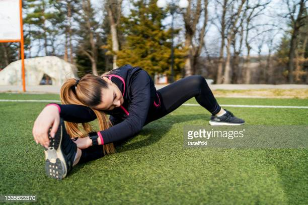 runner woman stretching - individual event stock pictures, royalty-free photos & images