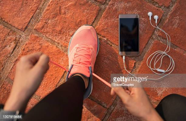 runner woman tying running shoes laces getting ready for race on run track with smartphone and earphones for music listening on mobile phone. athlete preparing for cardio training. feet on ground. - beginnings stock pictures, royalty-free photos & images