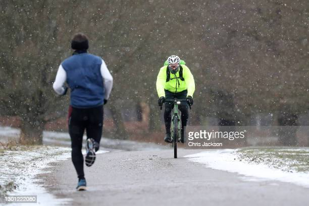 Runners and cyclists in the snow in Richmond Park on February 09, 2021 in London, England .