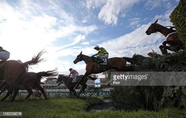 Runners and riders clear the water jump during the Randox Grand National Handicap Chase, on Grand National Day of the 2021 Randox Health Grand...