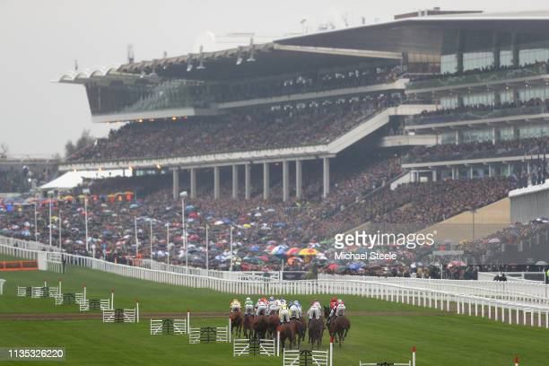 Runners and riders head towards the main grandstand in the opening race the Sky Bet Supreme Novices' Hurdles during Champion Day on day one of the...