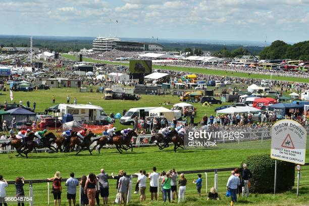 Runners and riders in the first race approach Tattenham Corner on the second day of the Epsom Derby Festival in Surrey, southern England on June 2,...