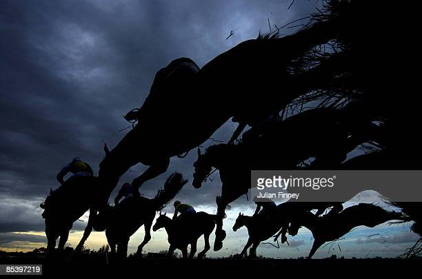 Runners and riders jump a fence in The Fulke Walwyn Kim Muir Challenge Cup Handicap Chase run during day three of the Cheltenham Festival at...