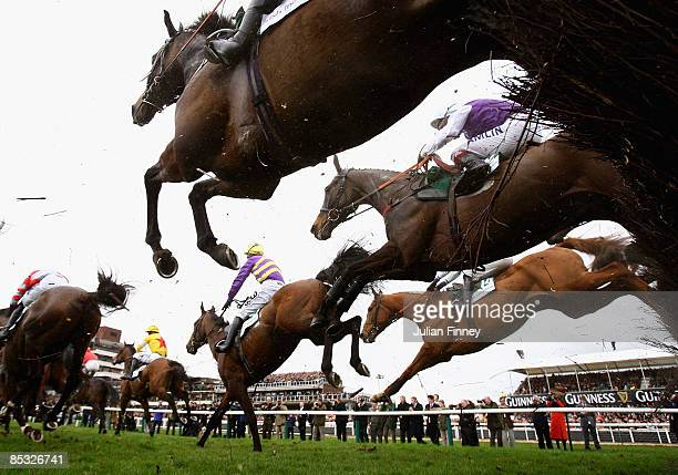 Runners and riders jump the third fence in The Irish Independent Arkle Challenge Trophy Steeple Chaseduring day one of the Cheltenham Festival at...