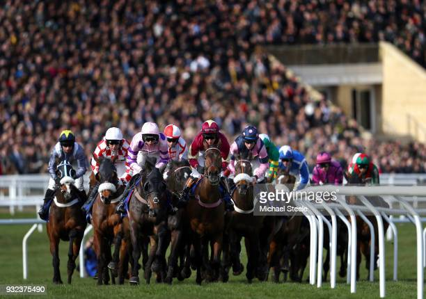 Runners and Riders pass the Main Stand during the Pertemps Network Final Handicap Hurdle at Cheltenham Racecourse on March 15 2018 in Cheltenham...