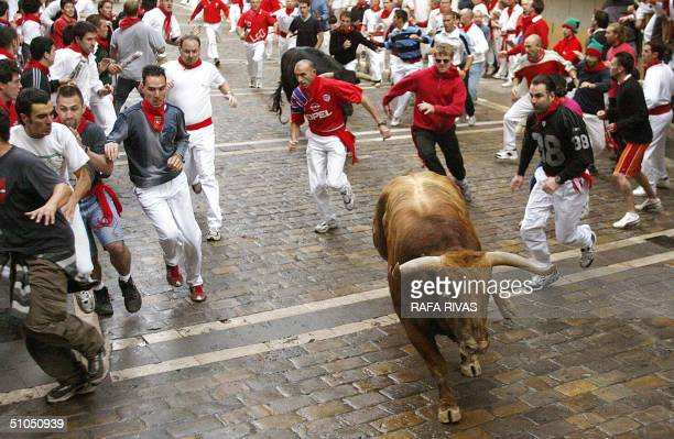Runners and two Jandilla bulls arrive at Estafeta street 12 July 2004 during the sixth 'encierro' of the San Fermin fair in the northern Spanish city...