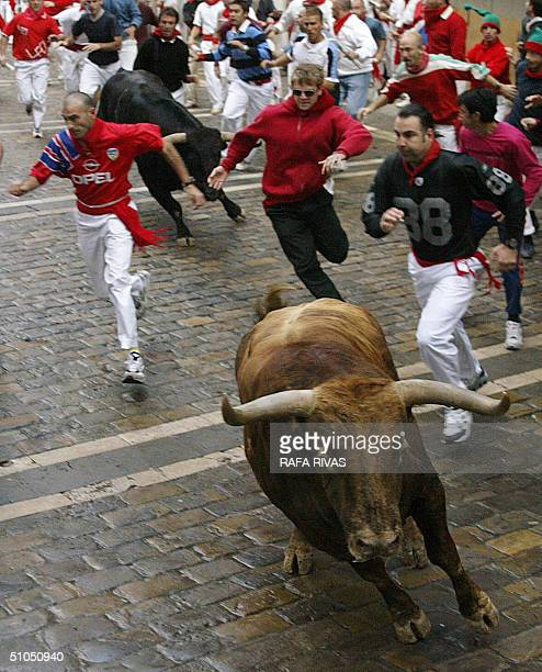 Runners and two Jandilla bulls arrive at Estafeta street 12 July 2004 during the sixth encierro of the San Fermin fair in the northern Spanish city...