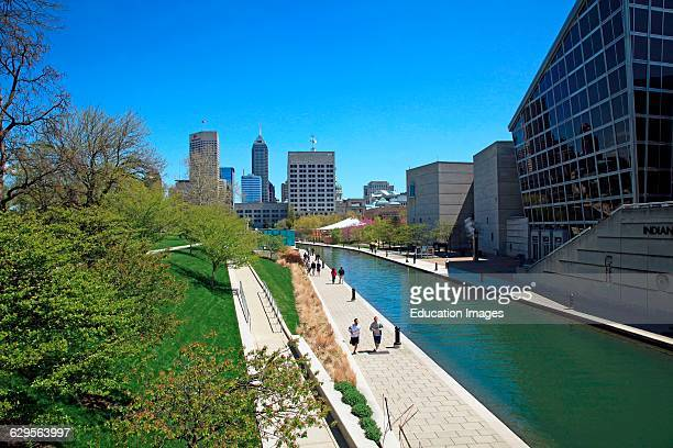 Runners and walkers enjoy a sunny spring day along the Canal Walk in the downtown area of Indianapolis Indiana The Canal Walk is a large linear park...